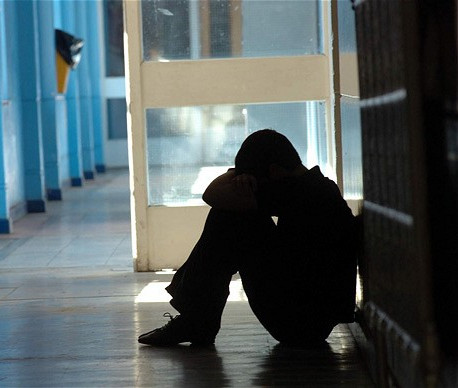 A bullied child cries in shadows next to school lockers