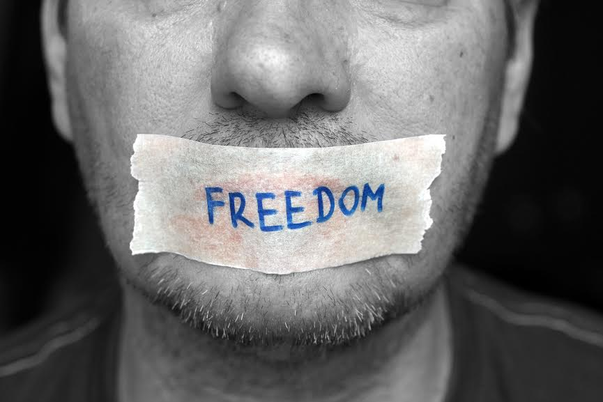 "A man's mouth is taped shut with the word ""freedom"" written on the tape"