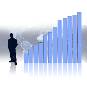 silhouette of a man standing next to a rising bar graph