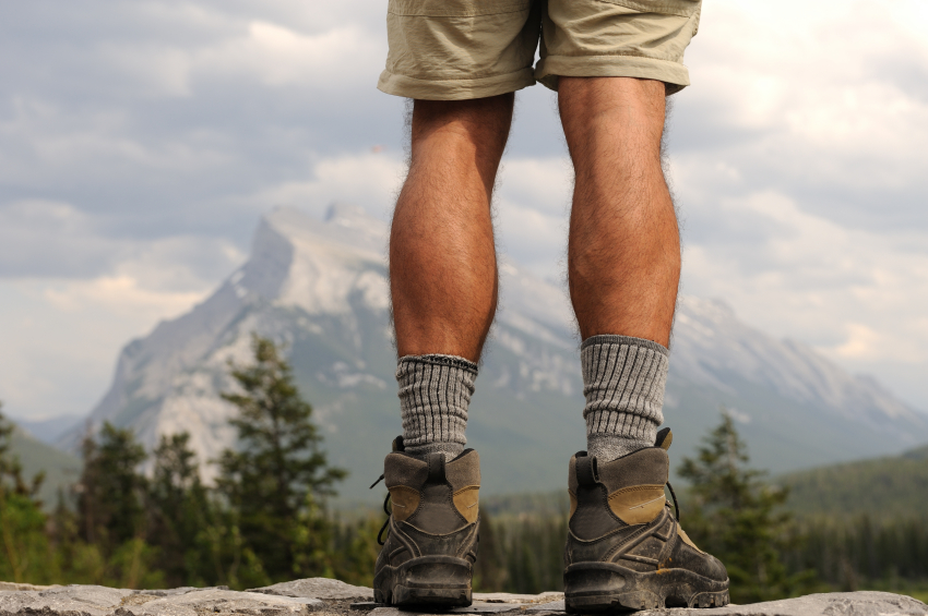 man in hiking clothes standing in mountain range