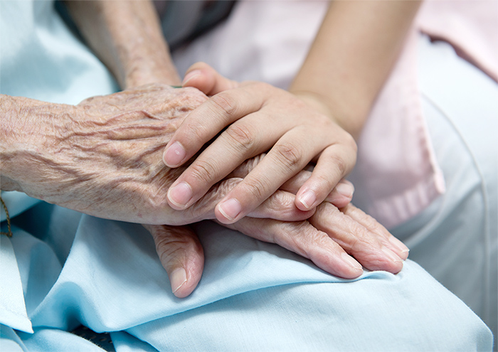 a young person holds the hands of an old person in hospice