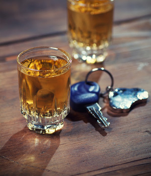 Two shots of whiskey sit next to a set of car keys