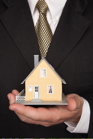 Man in a suit holds a miniature model of a house
