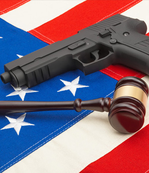 A gun and gavel rest on top of an American flag