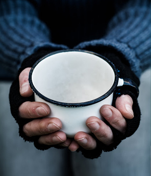 homeless person holds out empty cup