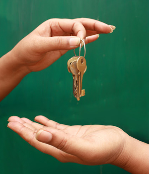 a person hands a set of house keys to another person