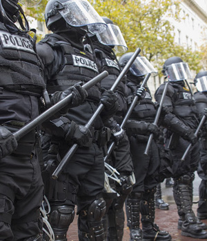 a SWAT team holds their batons at the ready