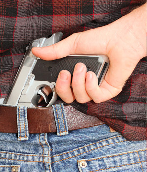 a man tucks a pistol into the back of his jeans