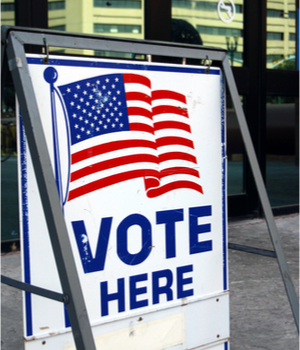 """a sign at a polling place reads, """"vote here"""""""