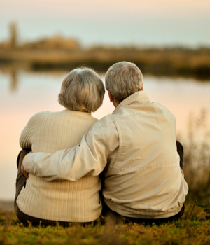elderly retired couple watch sunset