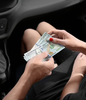 a man hands cash to a woman wearing fishnet stockings