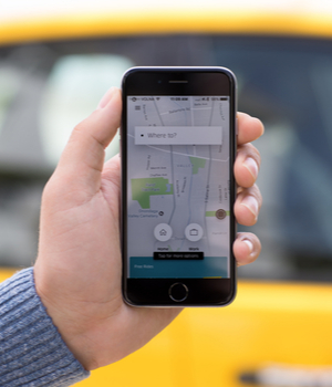 A person uses a ride sharing app on a smartphone