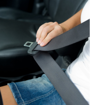 a young driver buckles their seat belt