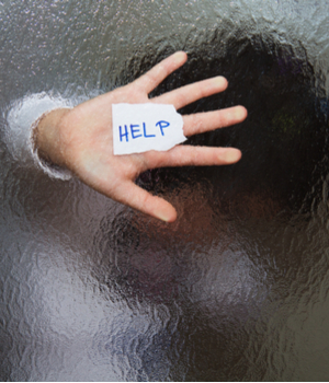 "a hand holds out a sign reading ""help"""