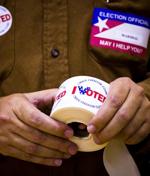 """An election worker holds a role of """"I voted"""" stickers"""