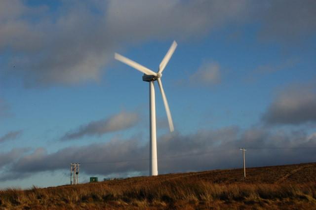 a wind turbine spins on a hill