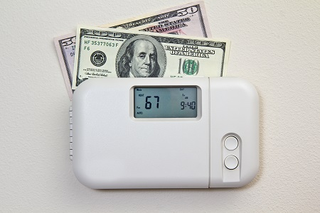 home thermostat with money representing energy costs