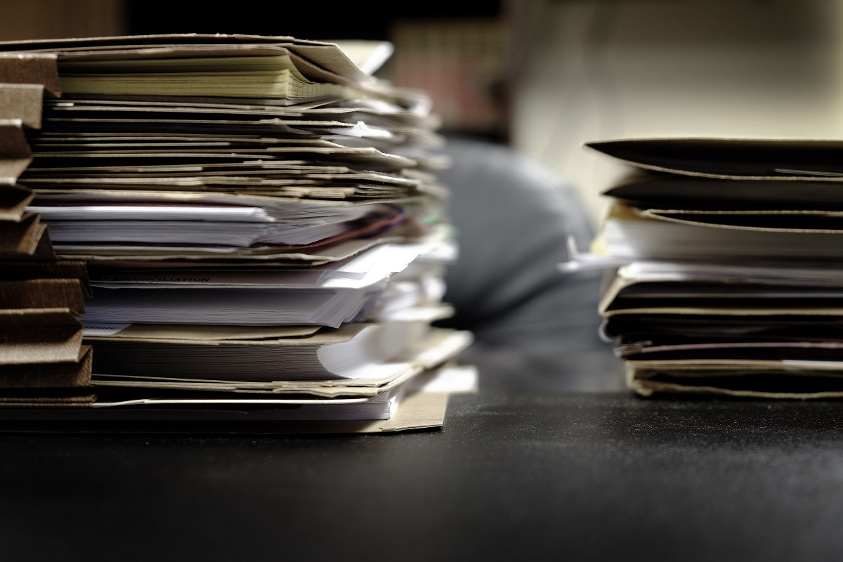 pile of bill request folders stacked on a table