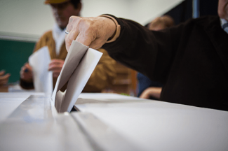 person voting inserting ballot into box