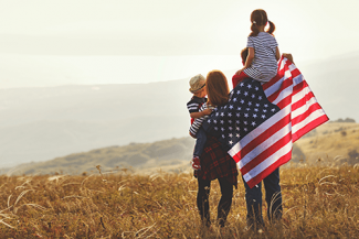 family in a field with a US flag